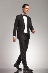 full body picture of an elegant man in tuxedo walking