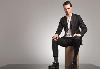 man in open tuxedo and undone bowtie sitting