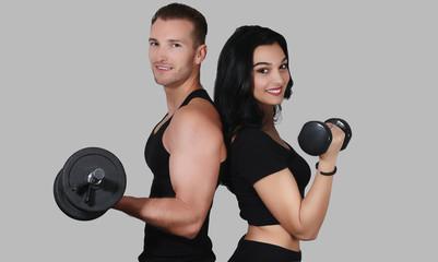 Jeune couple sportif tenant une haltère