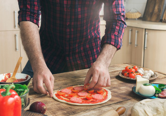 Man cooking pizza in home kitchen on wooden table