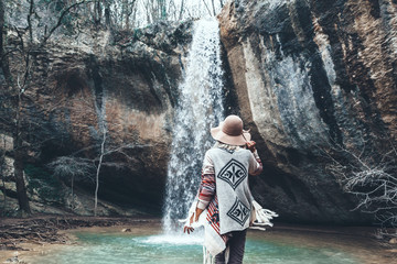 Human standing by the waterfall