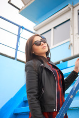 Portrait of brunette female in sunglasses over blue stairs.