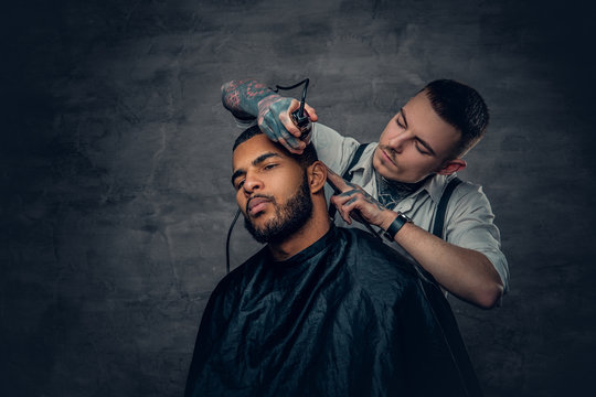 Male barber cutting the beard to Black stylish man.