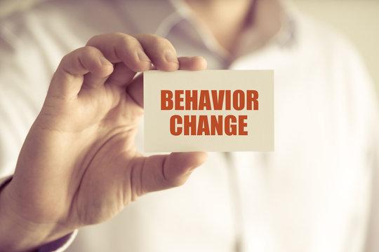 Businessman holding BEHAVIOR CHANGE message card