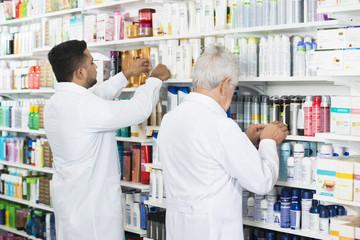 Multiethnic Chemists Arranging Stock On Shelves