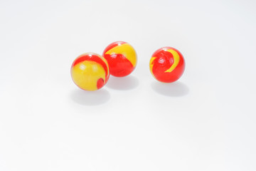 Three red yellow marbles isolated on white background