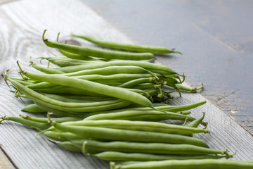 Bunch of green beans on the wooden background