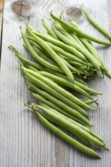 Pile of green beans on the wooden background