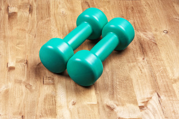 Two dumbbells for playing sports lie on a wooden surface
