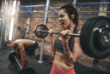 Fit couple lifting barbells in the gym.