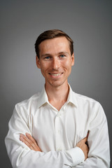 Business man in white shirt, portrait on grey background.