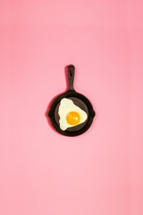 Tasty beautiful food fried egg in pan on fashionable pink background. Minimalistic Concept. Top...