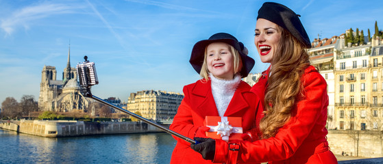 mother and child with christmas present box taking selfie, Paris