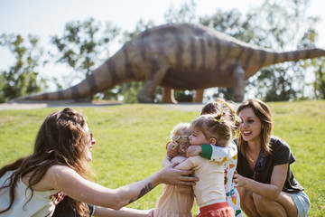 young girls play to the dinosaur park