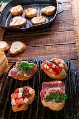 Set of bruschetta on black grill pan on wooden background. Tasty antipasto.