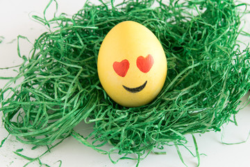 Happy easter: emoji as easter egg in green gras - heart shaped eye