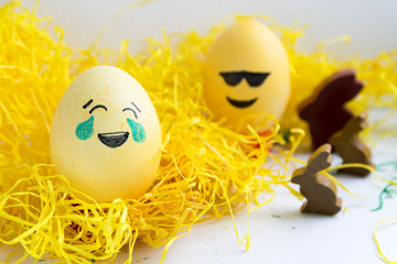 Happy easter: 2 emoji as easter egg in yellow gras with bunny - tears of joy and sunglasses