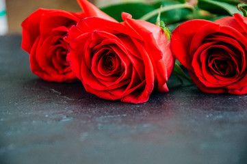 Three red roses over black stone background. Copy space. Close up.