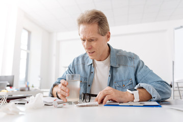 Worried man going to drink his medicine