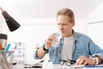 Disturbed man drinking useful medicine