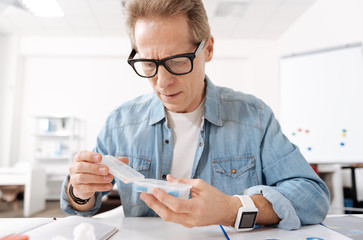 Confident elderly man holding box with pills