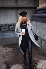 Young, hip and attractive blonde walking around the city with coffee to go, girl in a stylish hat and a gray coat