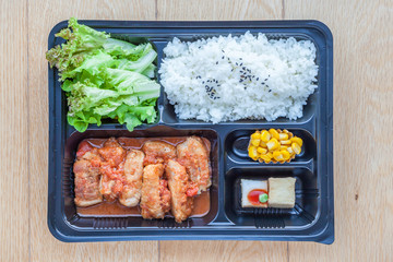 Top view of bento to-go plastic box, streamed Japanese rice with teriyaki grilled chicken in tomato sauce in lunch box.