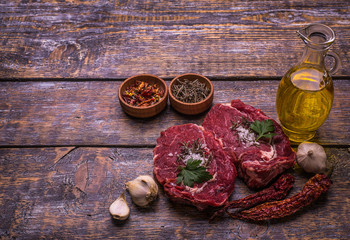 Raw Beef Steak, salt, pepper, garlic, rosemary, olive oil  on the black wooden board, background.
