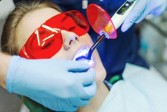 Close-up portrait of a female patient visiting dentist for teeth whitening in clinic