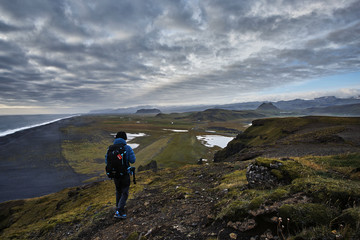 A man walking on top of Dyrholaey, Iceland