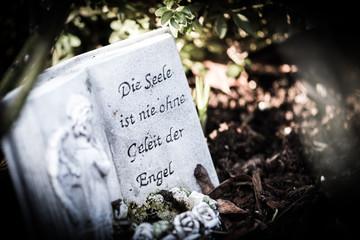 """Steinplatte mit der Inschrift """"Die Seele ist nie ohne Geleit der Engel"""" auf einem Grab"""