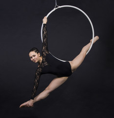 Aerial acrobat in the ring. A young girl performs the acrobatic elements in the air ring. Studio...