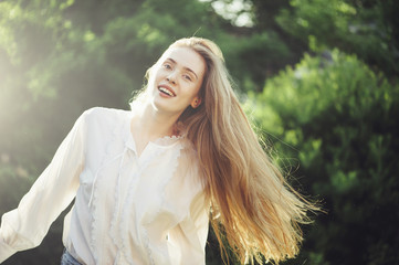 Beautiful happy redhead woman smiling outdoors in the park in the sunset