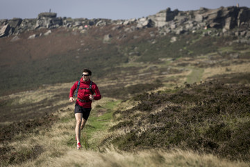 Male runner running near Stanage Edge, Peak District, Derbyshire, UK