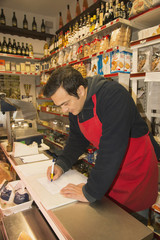 Mature male grocer writing notes in local italian grocery shop