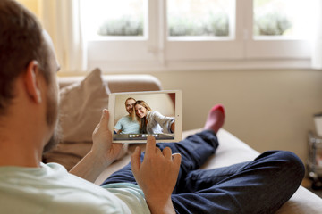 Man sitting on sofa, looking at photos on digital tablet, rear view