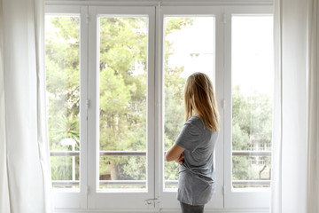 Woman at home, looking out of window, rear view