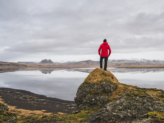 Man standing on rock, looking at view, Dyrholaos, Iceland