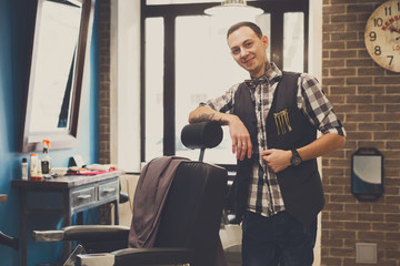 Barber invites to have seat on chair at barbershop