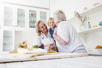 Senior woman, daughter and granddaughter preparing vegetables at kitchen table