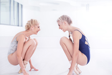 Two female ballet dancers practicing in dance studio, crouching opposite each other