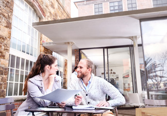 Businesswoman and man discussing paperwork on office patio
