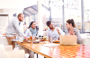 Businesswoman explaining to business team during working lunch in restaurant