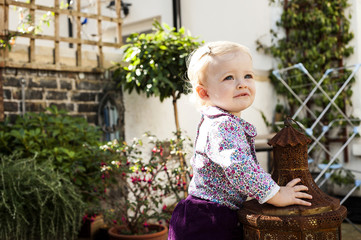 Baby girl standing while leaning on garden lantern