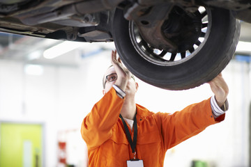 College mechanic student inspecting car wheel in repair garage