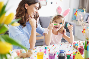 Woman and daughter painting easter eggs at table