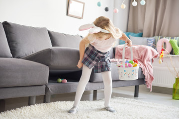 Girl finding easter eggs under sofa cushion