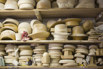 Stacked shelves with wooden moulds for headwear in workshop