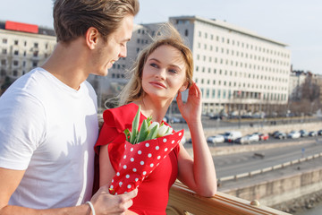 Young man dating with woman in red dress outdoor