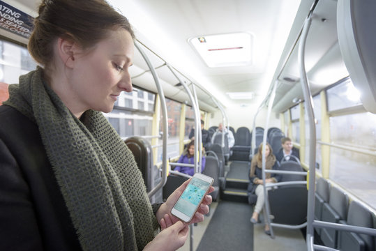 Passenger using smartphone to check map on electric bus